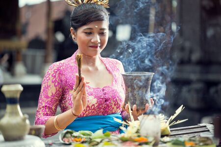 traditional scene of Balinese women praying with offering for Gods at the Hindu Temple Stock Photo