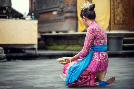young Balinese woman to praying in Hindu temple