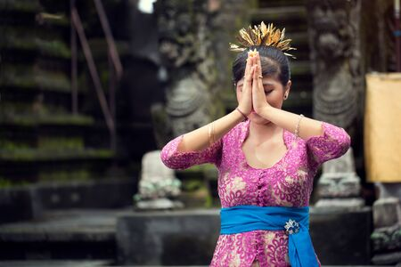 young woman is praying in Balinese temple during ceremony Stock Photo