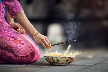 woman praying and  leaves gods offerings, every morning women bring flowers and incense to their gods Stock Photo