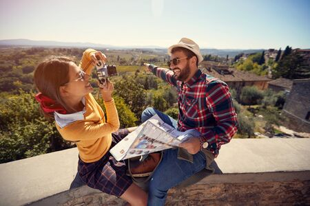 Smiling tourist man and girl using map as guide on vacation time and taking picture.