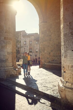 Happy man and girl taking pictures while enjoying in vacation on Italy.