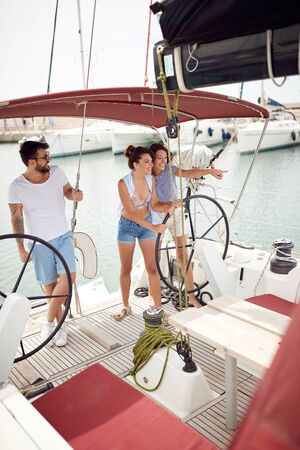 Happy friends on a sailboat at wheel going on ocean trip Banque d'images - 126343454