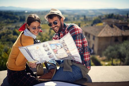 Smiling tourist man and girl using map as guide on journey time.