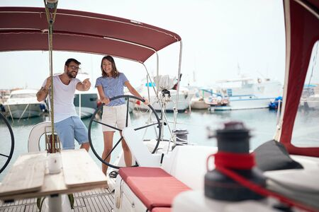Happy couple on a sailboat at wheel going on ocean trip Banque d'images - 126342387