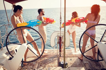 Group of happy people play on sailing boat with water pistols. Stock Photo