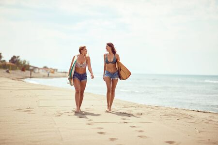 Surfing lifestyle. Fun sport on summer vacations. surfing girls in sexy bikini on the beach. 写真素材