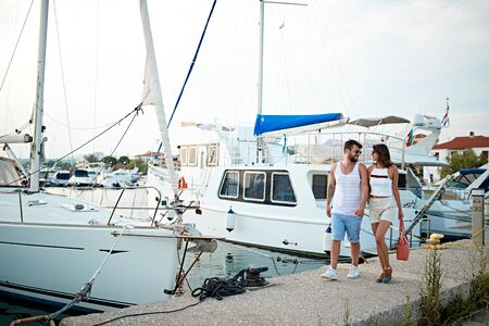 Romantic happy man and woman walking near the yachts on the dock.