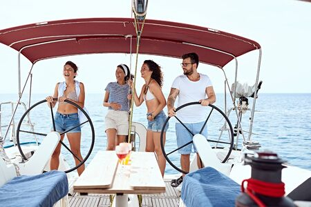 Happy young friends sailing in a sea on the yacht Stock Photo