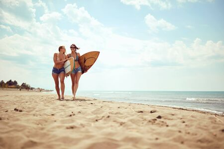 Happy friend's girls going to surfing. Healthy Active Lifestyle.