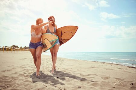 Healthy Active Lifestyle. Surfing. Summer Vacation. Happy surfer women's in bikini go to surfing. 写真素材