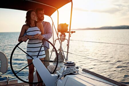 Romantic young couple sailing on the luxury boat together and enjoy at sunset Banque d'images - 127237861