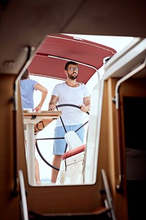Smiling man sailing on yacht - vacation, travel, sea, friendship and people concept