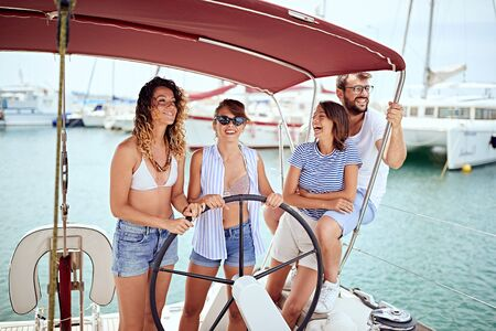 Vacation, travel, sea, friendship and people concept - Happy people enjoying a summer day on a boat