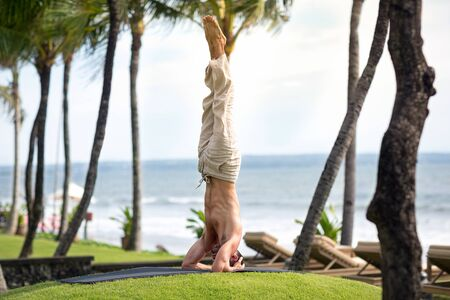 Man doing headstand pose in yoga Stock Photo