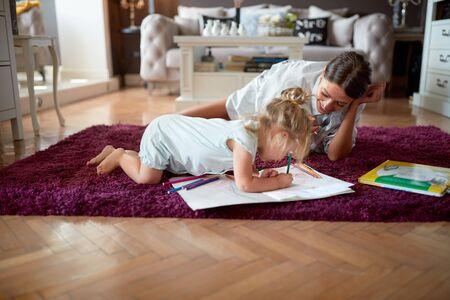 Niño con niñera dibujo en el suelo Foto de archivo