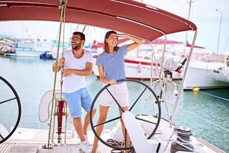 Happy man and woman on yacht at wheel going on ocean trip Banque d'images - 127236077