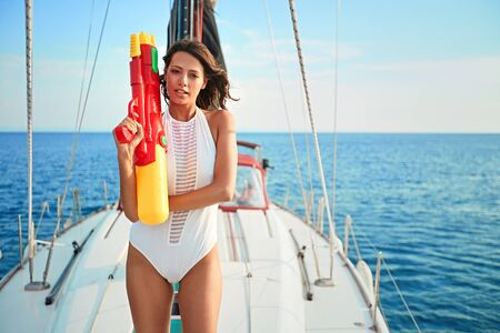 Young Woman on sailing boat with water pistols.