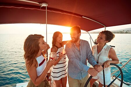 Young friends on vacation travel on boat together and have fun at sunset
