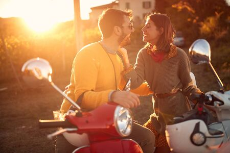 Happy young tourists on scooter enjoying in romantic road trip on vacation at sunset.