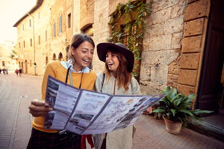 Two happy woman travel together. friends with map