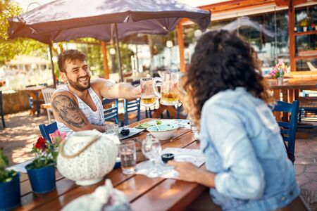 Beautiful loving couple sitting in a restaurant enjoying in beer and conversation Stok Fotoğraf