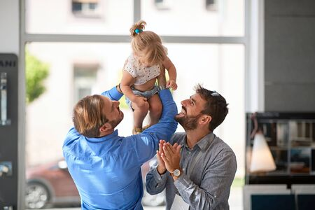 Smiling gay couple with child girl