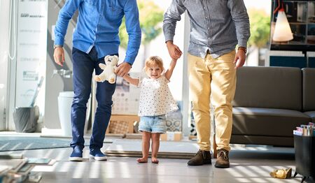 gay couple with smiling child girl in store for household Standard-Bild