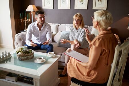 Female psychologist giving advice to couple in emotional problem
