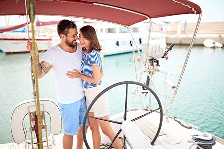 Smiling young couple on a yacht enjoy bright sunny day on vacation Banque d'images - 127833860