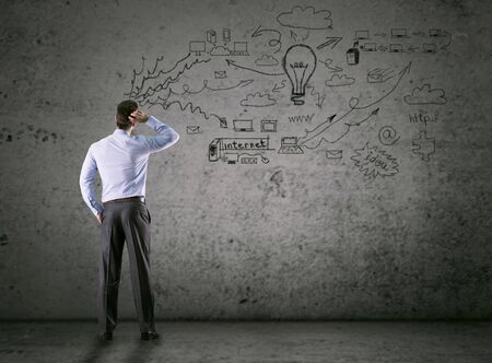 business concept, thinking man looking at drawing wall Stok Fotoğraf - 127833874