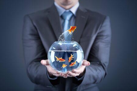 Geschäftsmannhand, die Goldfisch im Goldfischglas hält
