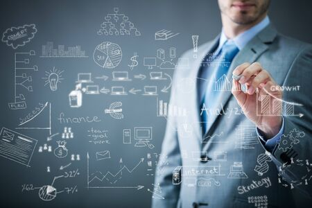businessman drawing business plan on transparent wall