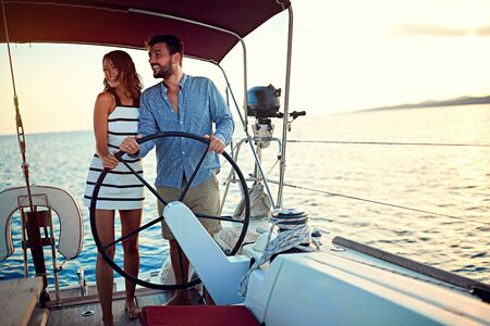 young couple sailing on the luxury boat together and enjoy at sunset Banque d'images - 127833940