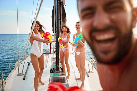 happy people play on sailing boat with water pistols at vacation.