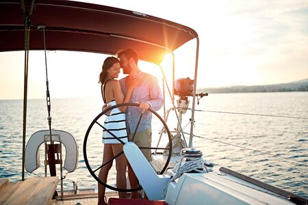 young man and woman sailing on the luxury boat together and enjoy at sunset on vacation Banque d'images - 127834176