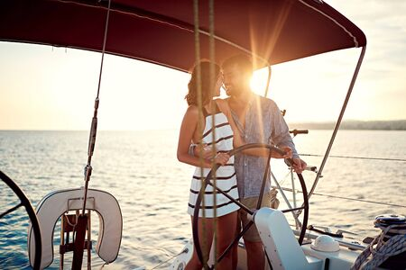 Romantic smiling couple on boat enjoy together at sunset Banque d'images - 127834192