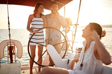 young smiling people have fun on the yacht at sunset.