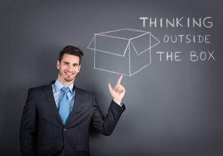 smiling businessman showing a drawing of think out of the box