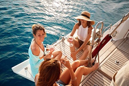 young friend's girl having party on sailing boat and drinking wine at summer day