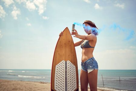 Smiling girl posing with her surfboard on the beach. Stock Photo