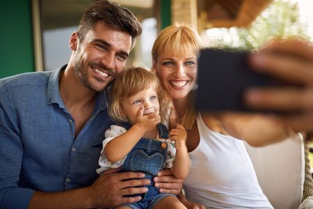 Young happy family making selfie portrait outdoor