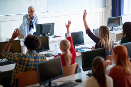 lecturer on class with young students in lecture hall Stock Photo