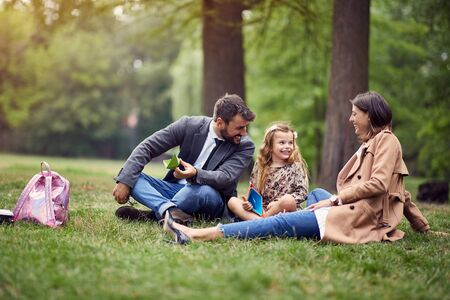 smiling business parents with a kid in park playing