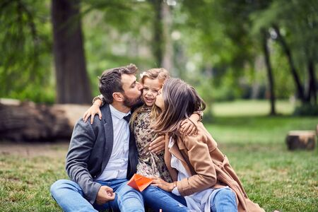 happy parents kissing there little child outdoor