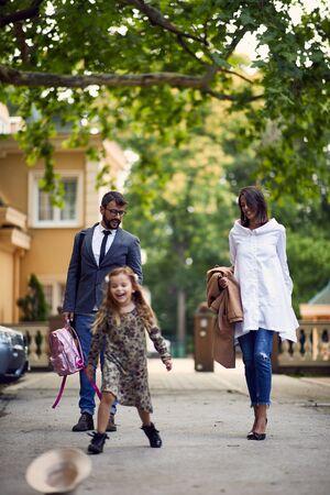padres de negocios jóvenes caminando con su hija después de la escuela