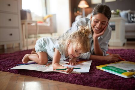 Adorable kid with young female drawing indoor