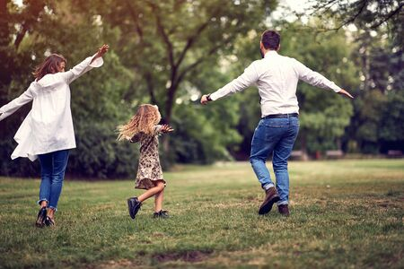 Happy parent with their kid girl after school in park playing together Imagens