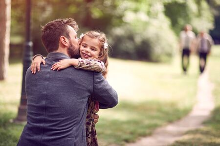 Happy school girl hugging their father after school Imagens