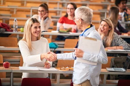 Smiling Student receiving an successful exam in a classroom 写真素材